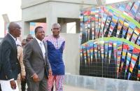 L'artiste Emmanuel Sogbadji auteur de la fresque -La paix t'accueille- expliquant son oeuvre au chef de l'État